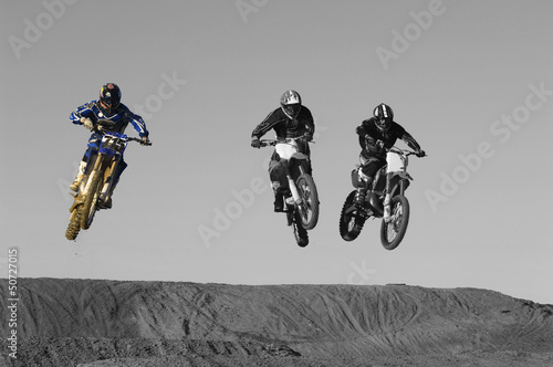 Young motocross racers riding on dirt track