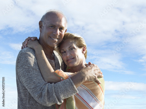 Portrait of smiling senior couple hugging each other against cloudy sky