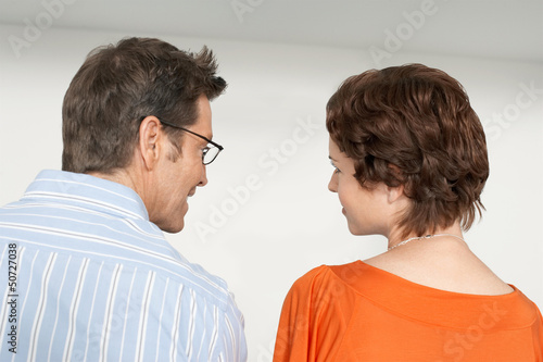 Back view of couple looking at each other against white wall