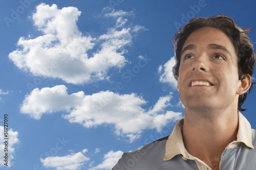 Smiling young man daydreaming against cloudy sky