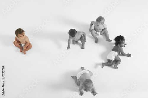 High angle view of baby girl looking at other babies crawling on floor