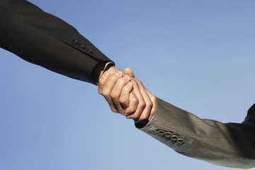 Businesspeople shaking hands against clear sky