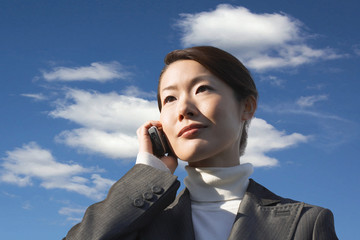 Young businesswoman using cell phone against cloudy sky