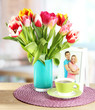 Beautiful tulips in bucket with cup of tea on table in room