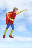 Boy dressed as superhero flying against cloudy sky