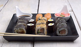 Sushi on the stone tray with chopsticks and soy sauce