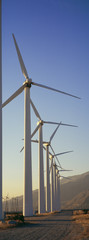 Row of power generating windmills in front of mountain range