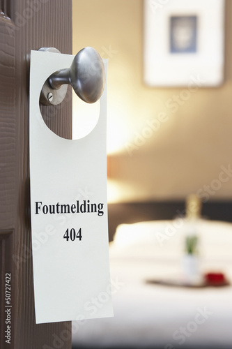 "Sign with Dutch text ""Foutmelding 404"" (error 404) hanging on hotel room door"