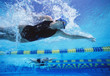 Professional female swimmers swimming in pool