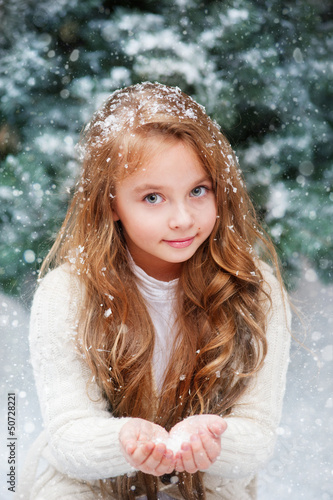 Beautiful liitle girl catches snowflakes
