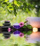 two candles and towels black stones and purple flower on water