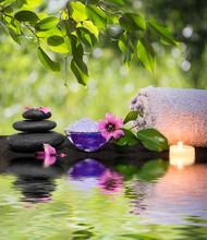 deux bougies et des serviettes pierres noires et fleur pourpre sur l'eau