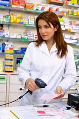 Gorgeous redhead pharmacist working with prescription