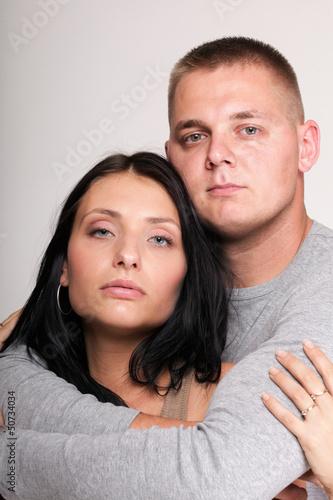 Beautiful pensive man woman stand near gray wal
