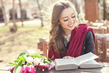 Beautiful brunette girl with a book outdoors