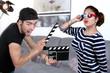 Jeune homme avec un clap de cinéma et une jeune actrice.