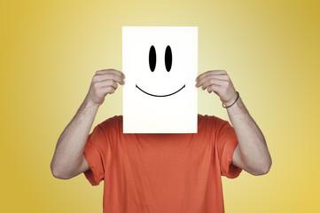 garçon montrant un papier blanc avec un émoticône heureux