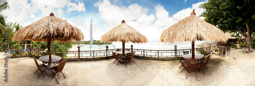 Tropical beach panorama with three umbrellas. Bali, Indonesia