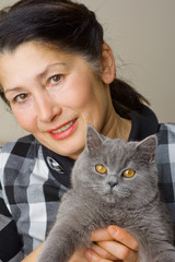 Pretty woman with a gray cat British breed