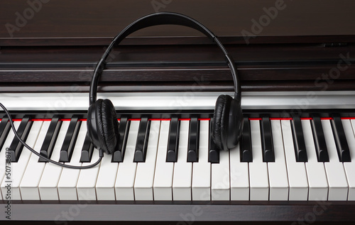 Earphones lie on a piano