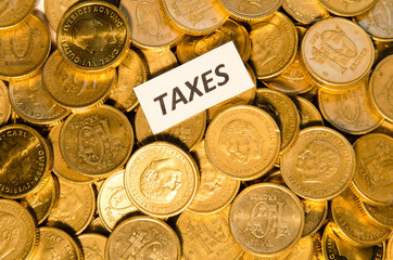 Taxes sign on golden coins
