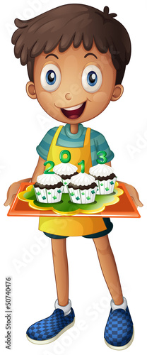 A boy holding a tray of cupcakes