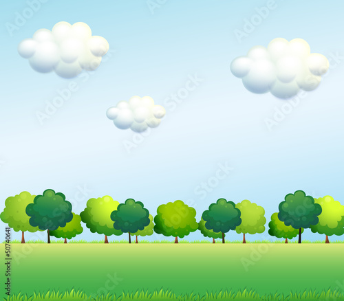 The green trees below the clear blue sky