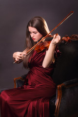 Beautiful girl playing a fiddle with eyes closed