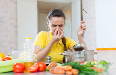 woman holding her nose because of bad smell from soup