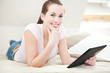 Attraktive junge Frau liegt auf dem Bett mit tablet-pc