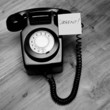 Black retro telephone with urgent reminder note