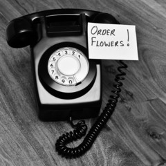 Black retro telephone with reminder note to order flowers