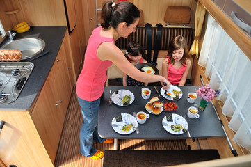 Family eating together in RV interior, travel in camper