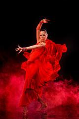Young woman dancing Latino on dark smoky background