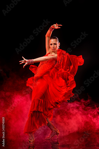 Young woman dancing Latino on dark smoky background
