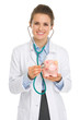 Medical doctor woman listening piggy bank with stethoscope