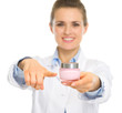 Smiling cosmetologist woman pointing on creme