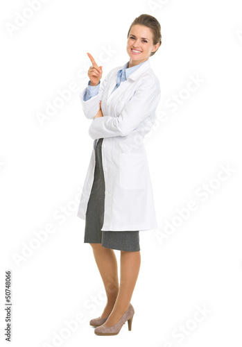 Full length portrait of woman in white robe pointing on copy spa