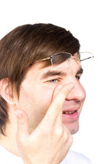 Closeup view of a man's brown eye while inserting a corrective c