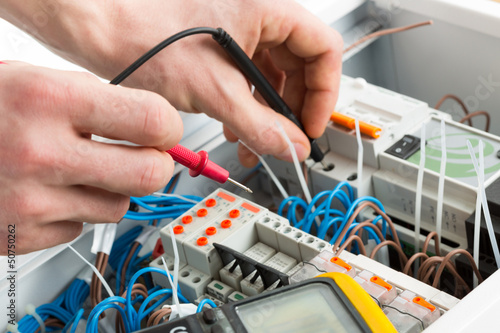 Hands of an electrician - 50750262