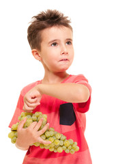 Little boy picks up the berry from bunch of grapes