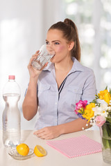 Beautiful young woman drinking a glass of water witth lemon