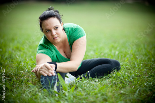 Plus sized woman stretching in a park. Shallow DOF.