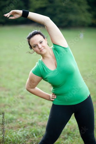 Overweight woman stretching in the park