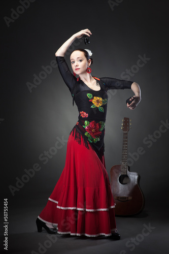 young woman dancing flamenco with castanets on black