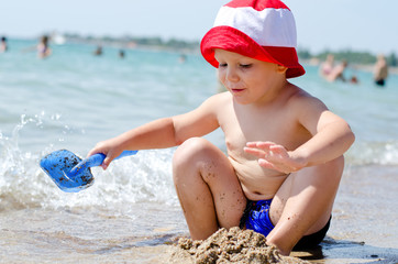 Little boy playing at the sea