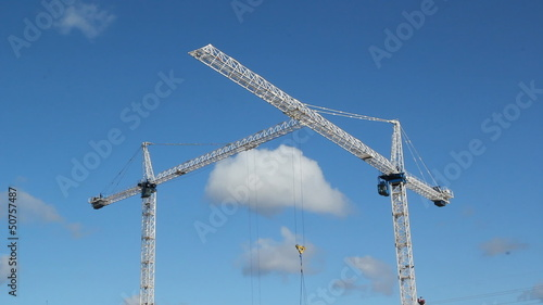 Two cranes. Trolley moves along jib of foreground crane.