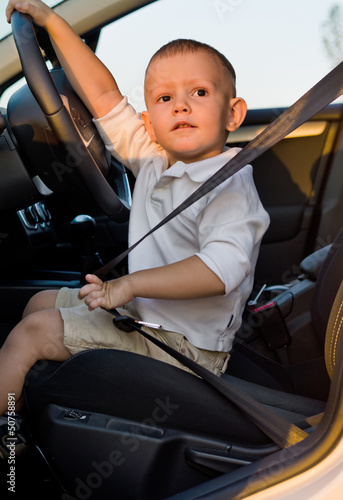 Cute little boy in the drivers seat of a car