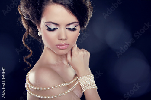 Beautiful woman with a pearl necklace on the bared shoulders