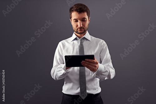 thoughtful businessman holding tablet pc